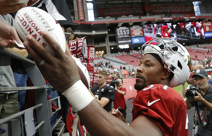 Arizona Cardinals running back David Johnson gives autographs to fans after an NFL football practice Saturday, Aug. 4, 2018, in Glendale. (Ross D. Franklin/AP)