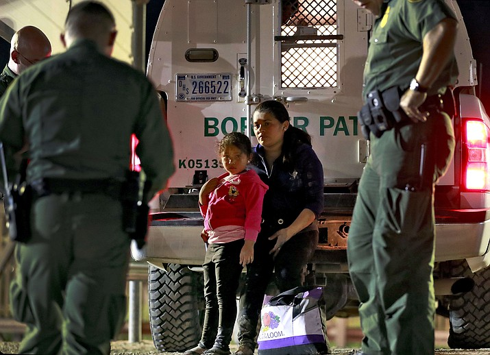 A mother and 5-year-old daughter from Honduras are detained by U.S. Customs and Border Patrol agents Wednesday, July 18, 2018, in San Luis, Ariz. The pair were apprehended by a U.S. Border Patrol agent who spotted them crossing a canal along the border with Mexico. (Matt York/AP)