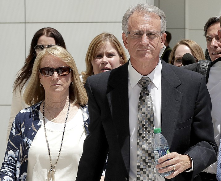 In this June 7, 2017, file photo, former Arizona Corporation Commissioner Gary Pierce, and his wife Sherry, left, leave court in Phoenix after being arraigned on bribery and fraud charges. Prosecutors said Tuesday, Aug. 7, 2018 that they are dropping the bribery case against Pierce, his wife and two others after their trial ended three weeks ago with a mistrial. (Matt York/AP, File)