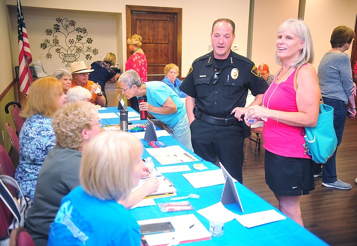 Prescott Valley Police Chief Bryan Jarrell, center, and Peggy Campbell meet some of the Block Watch captains in Stoneridge at the annual National Night Out in Prescott Valley Tuesday, Aug. 7, 2018.  (Les Stukenberg/Courier)