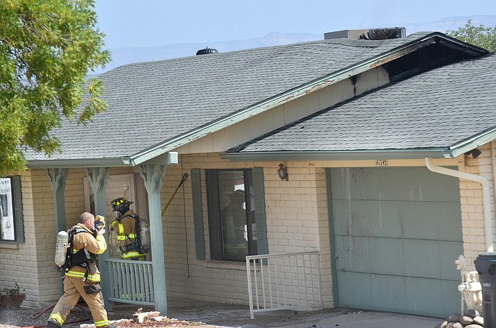 Firefighters inspect a home in Cottonwood Wednesday morning, Aug. 8, several hours after a lighting strike caused a fire in the home's attic.
