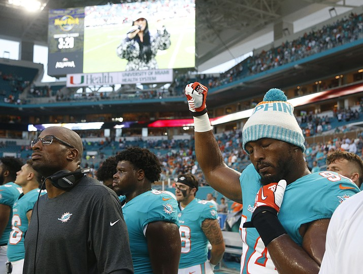 Miami Dolphins defensive end Robert Quinn (94) raises his right fist during the singing of the national anthem, before the team's NFL preseason football game against the Tampa Bay Buccaneers, Thursday, Aug. 9, 2018, in Miami Gardens, Fla. (Wilfredo Lee/AP)