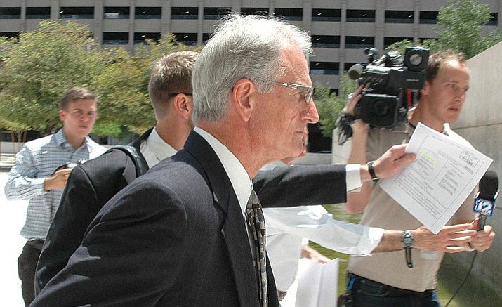 Former utility regulator Gary Pierce rushes past reporters last year following his initial court appearance. The U.S. attorney's office informed a judge in a court filing Tuesday that all charges will be dismissed. (Howard Fischer/Capitol Media Services file photo)