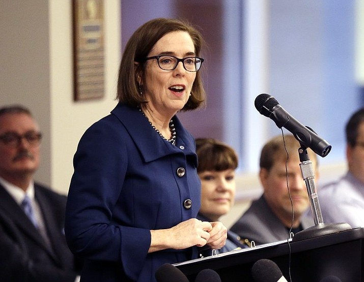 In this Feb. 2, 2018 file photo, Oregon Gov. Kate Brown speaks in Portland, Ore. The evangelist Franklin Graham recently asked thousands of people at an Oregon rally to pray for the state's Democratic governor, saying she should be a Christian. Yoga and meditation suit Brown just fine, she told reporters Thursday, Aug. 9, 2018, when asked if she follows a certain faith. (AP Photo/Don Ryan, File)