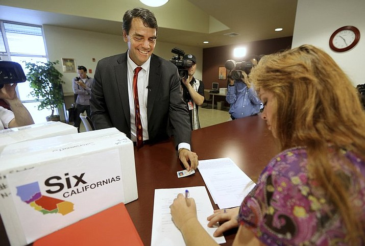 In this July 15, 2014 file photo, Silicon Valley venture capitalist Tim Draper presents his drivers license for identification purposes to Heather Ditty, elections manager for the Sacramento County Registrar of Voters, as he turns in boxes of petitions for a ballot initiative that would ask voters to split California into six separate states in Sacramento, Calif. The court struck venture capitalist Draper's initiative from the ballot in July 2018 as part of a legal challenge in response to a lawsuit but didn't rule on the merits of the case. Draper says he's giving up on the effort after the state Supreme Court knocked it off the November 2018 ballot. (AP Photo/Rich Pedroncelli, File)