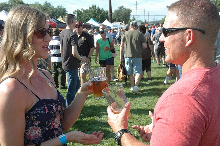 Kris Little and Eric Hatchell take in the Mile High Brewfest — and a couple beers — Saturday, Aug. 11, 2018, held at Prescott Mile High Middle School. (Jason Wheeler/Courier)
