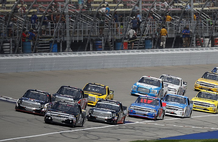 Pole sitter John Hunter leads the field at the start of a NASCAR truck series race at Michigan International Speedway in Brooklyn, Mich., Saturday, Aug. 11, 2018. (Paul Sancya/AP Photo)
