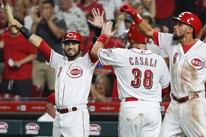 Cincinnati Reds' Eugenio Suarez (7) and Curt Casali (38) celebrate after scoring on an RBI-double by Tucker Barnhart off Arizona Diamondbacks relief pitcher Archie Bradley in the eighth inning of a baseball game, Saturday, Aug. 11, 2018, in Cincinnati. (John Minchillo/AP Photo)