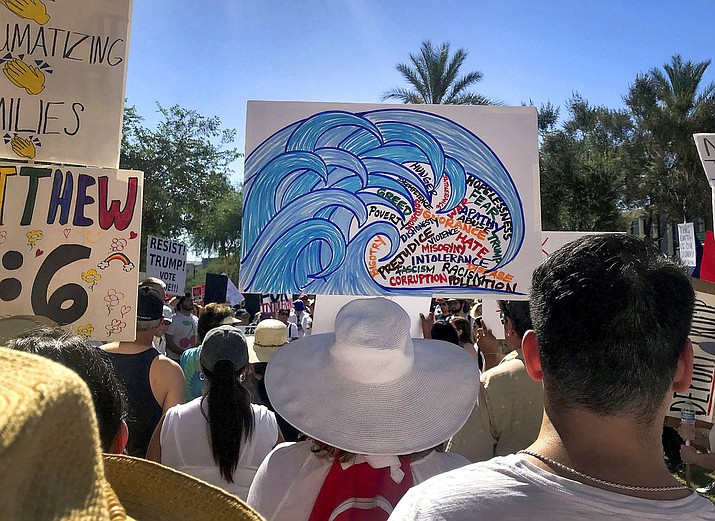 In this June 30, 2018, photo, protesters rally at a Keep Families Together march at the Arizona state Capitol in Phoenix. The blue wave Democrats hope will crash into Arizona this November is creeping up in community centers, library auditoriums and churches. (AP Photo/Melissa Daniels)
