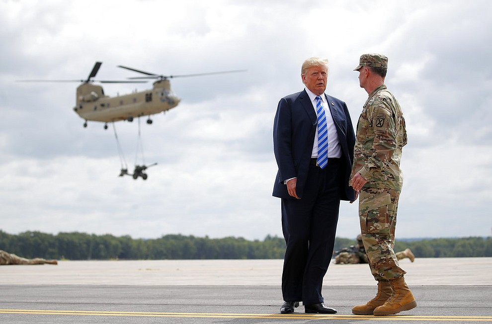 President Donald Trump talks with Maj. Gen. Walter Piatt as they watch an air assault exercise at Wheeler-Sack Army Air Field in Fort Drum, N.Y., Monday, Aug. 13, 2018, (AP Photo/Carolyn Kaster)