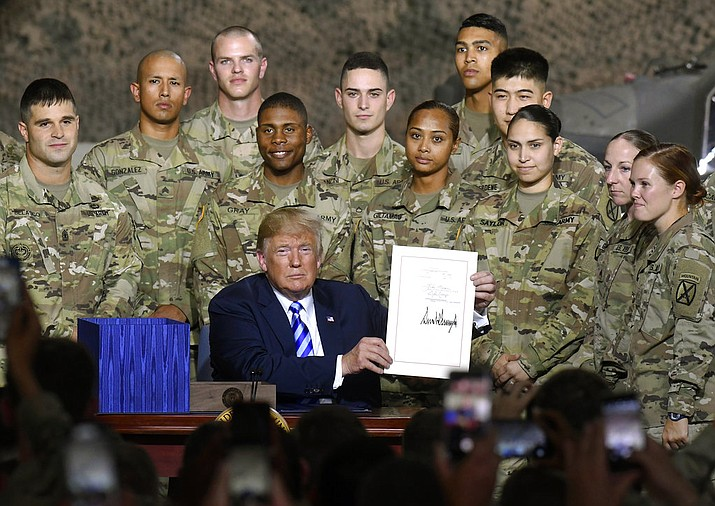 President Donald Trump signs the John McCain National Defense Authorization Act for the Fiscal Year 2019, during a signing ceremony Monday, Aug. 13, 2018, in Fort Drum, N.Y. (AP Photo/Hans Pennink)