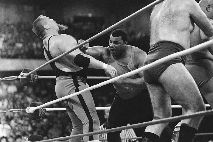 "Chicago Bears' William Perry, right, landing a punch on pro wrestler Jim ""The Anvil"" Neidhart during the ""Over-The-Top-Rope"" battle royal at Wrestlemania 2 in Rosemont, Illinois, April 7, 1986. Neidhart, who joined with Bret Hart to form one of the top tag teams in the 1980s with the WWE, has died. He was 63. The Pasco Sheriff's Office said Neidhart fell at home, hit his head and ""succumbed to his injury"" on Monday, Aug. 13, 2018, in Wesley Chapel, Florida. No foul play was suspected. (Charlie Bennett/AP Photo, file)"
