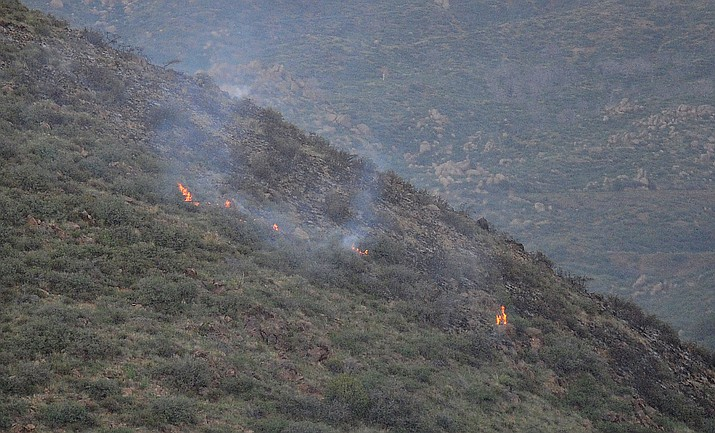 Flames pop up intermittently as a small wildland fire started at the western end of Doce Pit Road north of Prescott Tuesday, August 14, 2018.  (Les Stukenberg/Courier)