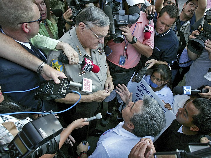 In this July 14, 2006, file photo, Elias Bermudez kneels before then-Sheriff Joe Arpaio at a protest over the lawman's immigration crackdowns in Phoenix. Bermudez, who led the pro-immigrant group Immigrants Without Borders, is asking a judge to move his Sept. 5. 2018 trial on tax charges out of Arizona, citing publicity about the charges and his past advocacy efforts. He has pleaded not guilty to the charges. (Matt York/AP, file)