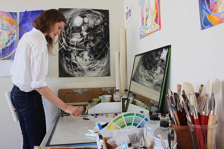 Anna Fox Ryan, new program director for the ArtHub in downtown Kingman, mixes paint at her studio workplace. ArtHub is holding a farewell reception for its summer artists-in-residence at 5 p.m. Friday. (Hubble Ray Smith/Daily Miner)
