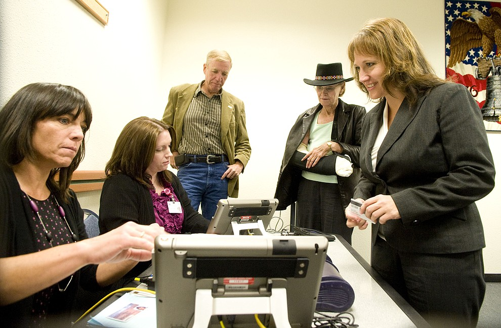 Yavapai County Election officials Jimmie Jo Hlavin and Desi Zurcher, at right, demonstrate to Yavapai County Supervisors Thom Thurman and Carol Springer along with County Administrator Julie Ayers show a new Voting Center would work on Monday during a special presentation at the County Administration Building in Prescott November 14, 2011. (Les Stukenberg/Courier)