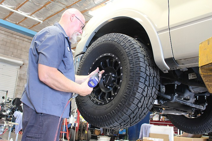 Eric Stolze starts work Thursday on installing a lift kit on a customer's truck at Great West Customs. Service-providing industries lost 100 jobs in Mohave County in July, according to the Office of Economic Opportunity. (Hubble Ray Smith/Daily Miner)
