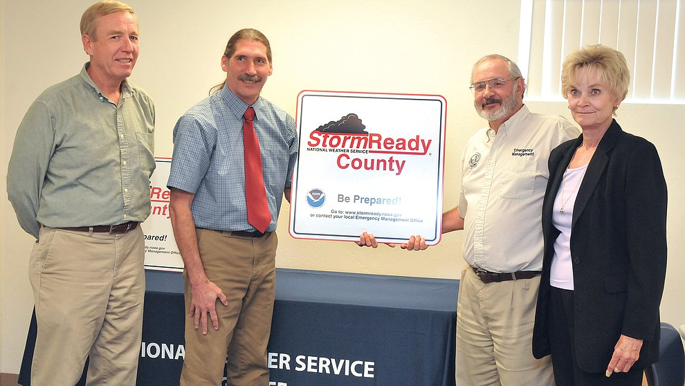 Yavapai County Supervisors Tom Thurman and Carol Springer look on as National Wether Service Falgstaff's Warning Coordination Meteorologist George Howard presents Yavapai County Emergency Management Coordinator Nick Angiolillo with a sign designating Yavapai County as Storm Ready August 24, 2009. (Les Stukenberg/Courier)