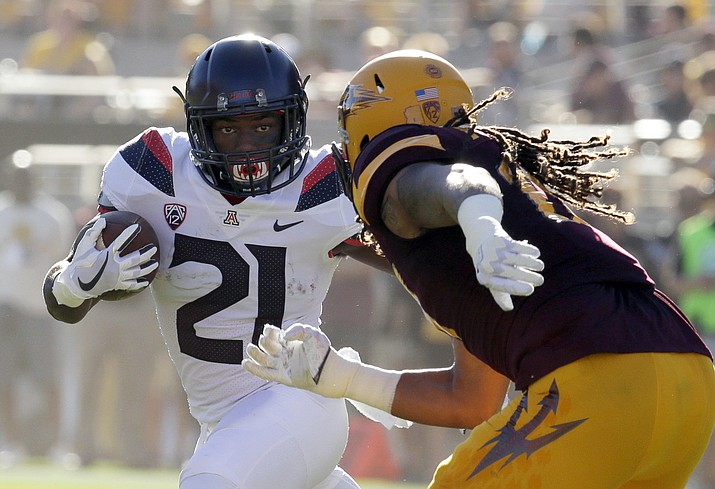 In this Nov. 25, 2017, file photo, Arizona running back J.J. Taylor (21) tries  to run the ball around Arizona State defensive back J'Marcus Rhodes in the first half in Tempe. (Rick Scuteri/AP, file)