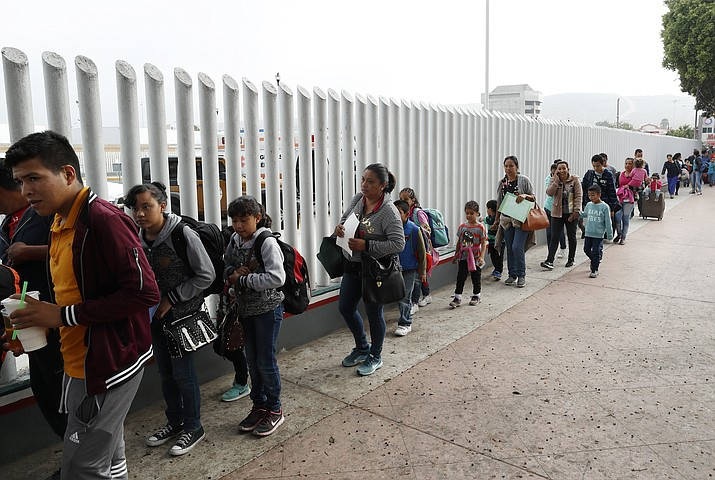 This July 26, 2018 file photo shows people lining up to cross into the United States to begin the process of applying for asylum near the San Ysidro port of entry in Tijuana, Mexico.A federal judge has extended a freeze on deporting families separated at the U.S.-Mexico border, giving a reprieve to hundreds of children and their parents to remain in the United States. (Gregory Bull/AP, File)