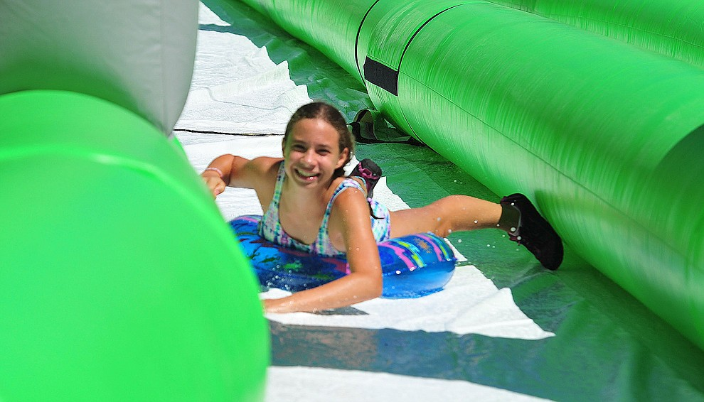 Aliviah Wnenta from Phoenix comes down the 600+ foot water slide at the Monsoon Festival in downtown Prescott Saturday, August 18, 2018. Wnenta was in town with her six cousins to visit her grandparents. (Les Stukenberg/Courier)