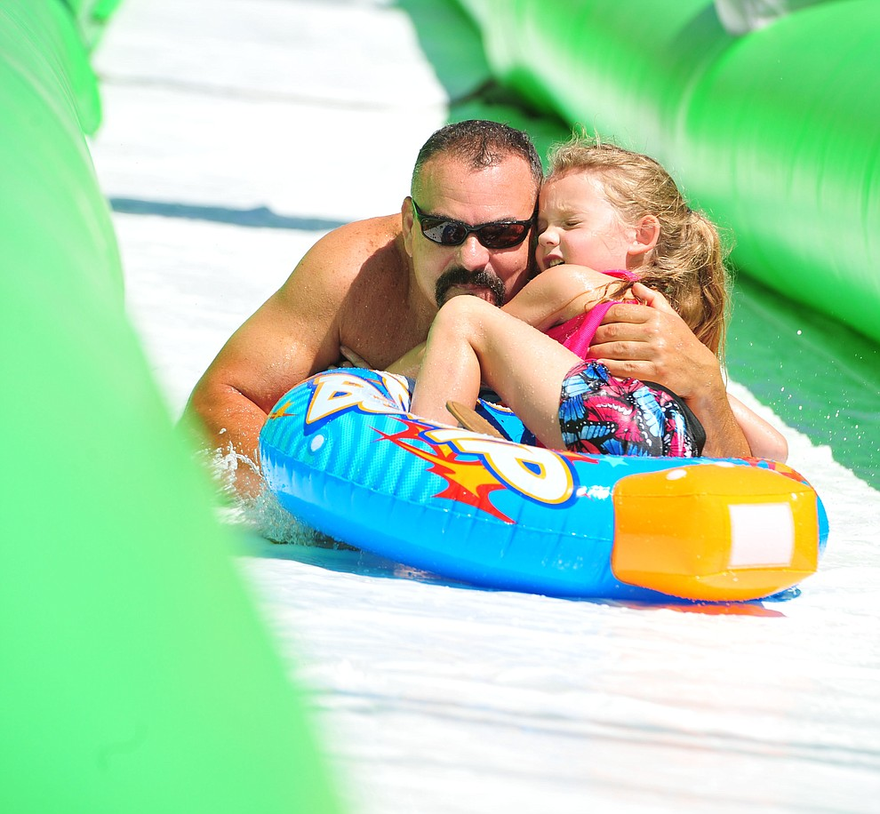 David and Arya Cutrer come down the 600+ foot water slide at the Monsoon Festival in downtown Prescott Saturday, August 18, 2018.  (Les Stukenberg/Courier)