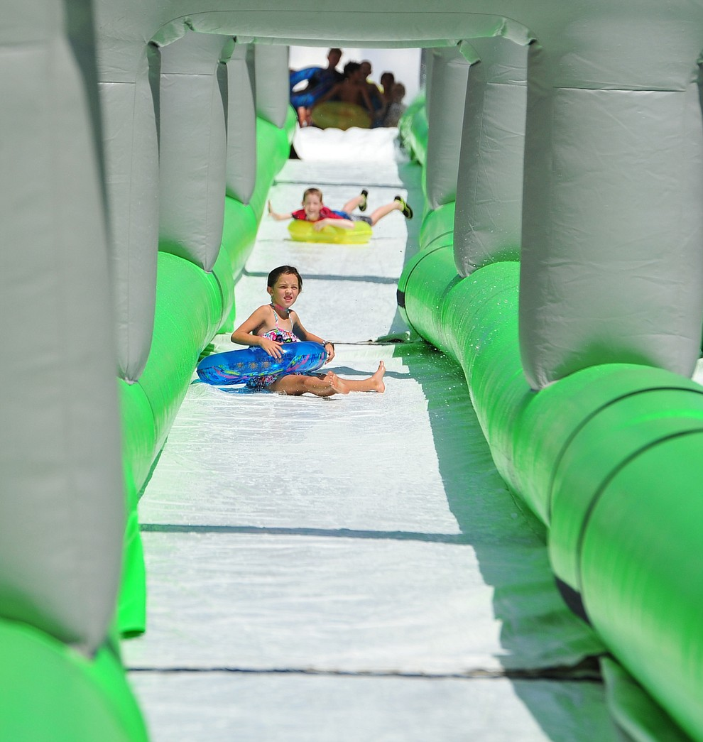 Sophia Stukenberg and Ronan Houts come down the 600+ foot water slide at the Monsoon Festival in downtown Prescott Saturday, August 18, 2018.  (Les Stukenberg/Courier)