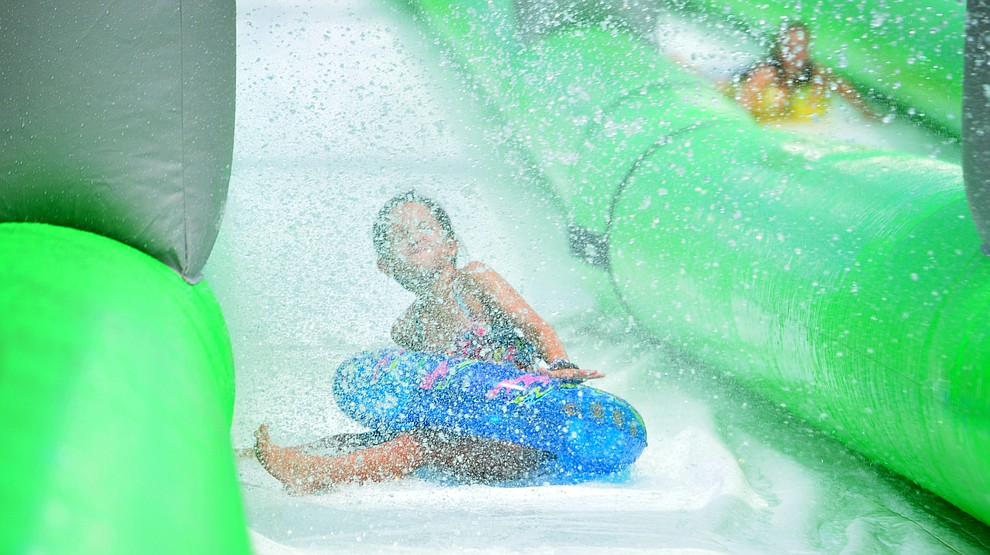 A rider gets splashed with by a hose coming down the 600+ foot water slide at the Monsoon Festival in downtown Prescott Saturday, August 18, 2018.  (Les Stukenberg/Courier)