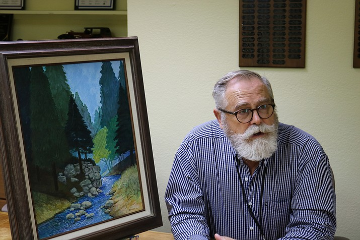 "PSA Art Awakenings artist in residence Paul VerBurg discusses his piece ""Mountain Idyll,"" which can be won by entering into the Kingman Area Chamber of Commerce raffle. (Photo by Travis Rains/Daily Miner)"