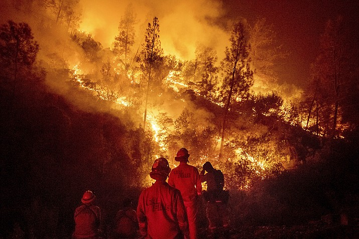 Firefighters monitor a backfire while battling the Ranch Fire, part of the Mendocino Complex Fire near Ladoga, California, Aug. 7, 2018. The years with the most acres burned by wildfires have some of the hottest temperatures, an Associated Press analysis of fire and weather data found. As human-caused climate change has warmed the world over the past 35 years, the land consumed in flames has more than doubled. (Noah Berger/AP Photo, file)