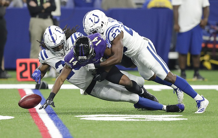 Baltimore Ravens wide receiver Tim White (14) fumbles on a punt return as he is hit by Indianapolis Colts defensive back Clayton Geathers (26) and cornerback Kenny Moore (23) in the first half of an NFL preseason football game in Indianapolis, Monday, Aug. 20, 2018. (Michael Conroy/AP Photo)