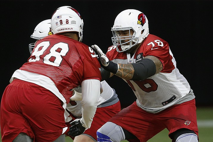Arizona Cardinals offensive guard Mike Iupati (76) blocks defensive tackle Corey Peters, right, during an NFL football practice Monday, Aug. 13, 2018, in Glendale. (Ross D. Franklin/AP Photo)