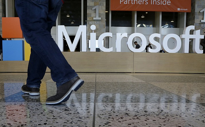 In this April 28, 2015, file photo, a man walks past a Microsoft sign set up for the Microsoft BUILD conference at Moscone Center in San Francisco. Microsoft has uncovered new hacking attempts by Russia targeting U.S. political groups ahead of the midterm elections. The company said Tuesday, Aug. 21, 2018, that a group tied to the Russian government created fake websites that appeared to spoof two American conservative organizations: the Hudson Institute and the International Republican Institute. Three other fake sites were designed to look as if they belonged to the U.S. Senate. (Jeff Chiu/AP, file)