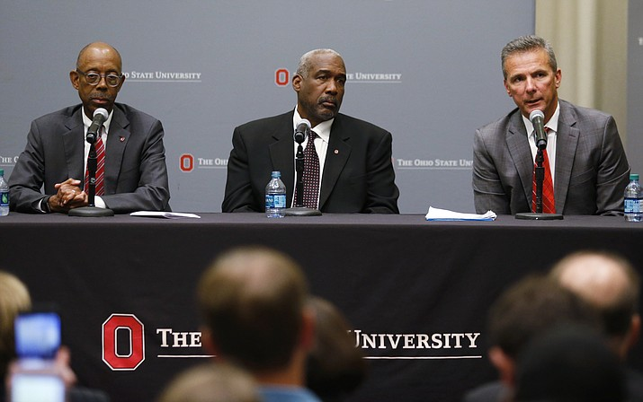 Ohio State football coach Urban Meyer, right, answers questions as athletic director Gene Smith and university President Michael Drake, left, listen during a news conference in Columbus, Ohio, Wednesday, Aug. 22, 2018. (Paul Vernon/AP)