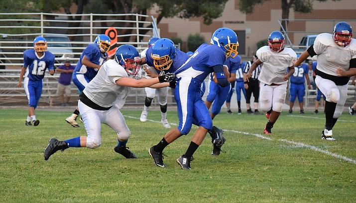 Camp Verde junior Josh Lake  pulls down a Sanders Valley player during their scrimmage last week. The Cowboys open the season on Friday at Scottsdale Prep. VVN/James Kelley