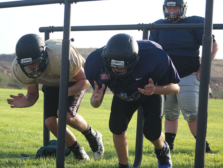 Kingman Academy linemen run drills during practice. The Tigers will depend on the big men up front to protect quarterback Dallas Edwards in the season opener Saturday against Utah's Canyon View. (Photo by Beau Bearden/Daily Miner)
