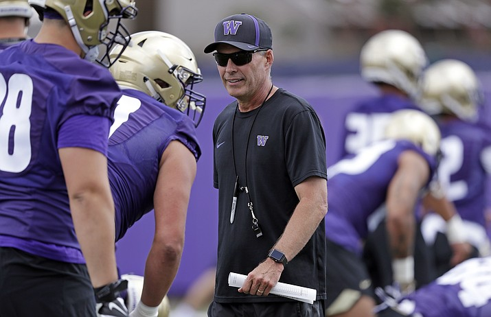 This Aug. 3, 2018, file photo shows Washington head coach Chris Petersen walking on the field during a team football practice in Seattle. Petersen's Huskies are the preseason favorites to win the Pac-12 with their roster full of NFL-caliber talent, but the entire league is looking for an improved season after going 1-8 in bowl games last winter. (Elaine Thompson/AP, file)