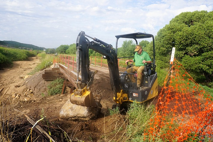 Prescott Recreation Services Director Joe Baynes works to move a large boulder into place alongside the old railroad bridge that was washed out on the Peavine Trail in a July microburst storm. (Cindy Barks/Courier)