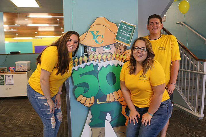 Resident hall assistants pose next to an image of Yavapai College's new mascot, Ruff, during Yavapai College's residence hall move-in day, Saturday, Aug. 18, 2018. Left to right: Dasha Weston-Rhoades, Kaylee Berisford, and Jake DeSousa. (Jennifer McCormack, Yavapai College/Courtesy)