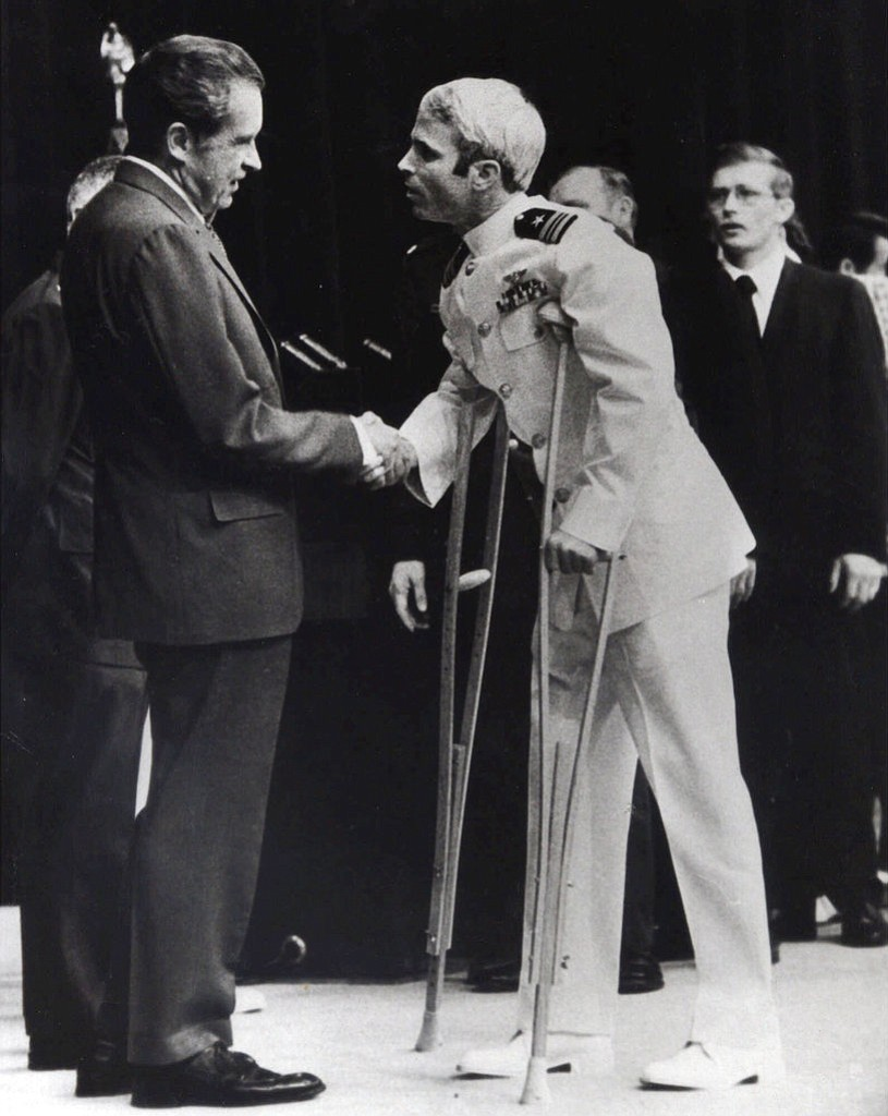 FILE - In this May 25, 1973, file photo, U.S. Navy Lt. Cmdr. John McCain is greeted by President Richard Nixon, left, in Washington, after McCain's release from a prisoner of war camp in North Vietnam. An aide says that McCain died Saturday, Aug. 25, 2018. He was 81. (AP Photo/Harvey Georges, File)