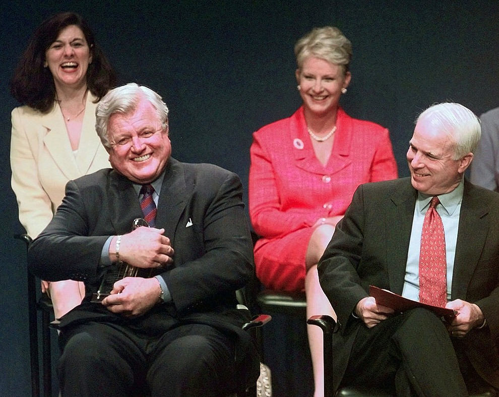 FILE - In this May 24, 1999, file photo, Sen. Edward Kennedy, D-Mass., jokingly holds the Profile in Courage award as if he intends to keep it, as co-winner, Sen. John McCain, R-Ariz., looks on at right during a ceremony at the John F. Kennedy Library in Boston. In back row are their spouses, Victoria Kennedy, left, and Cindy McCain. Arizona Sen. McCain, the war hero who became the GOP's standard-bearer in the 2008 election, has died. He was 81. His office says McCain died Saturday, Aug. 25, 2018. He had battled brain cancer. (AP Photo/Elise Amendola, File)
