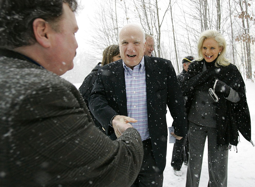 FILE - In this Jan. 1, 2008, file photo, Presidential hopeful Sen. John McCain, R-Ariz., center, and his wife, Cindy, greet Richard Brothers on their way to a house party in Tilton, N.H. Aide says senator, war hero and GOP presidential candidate McCain died Saturday, Aug. 25, 2018. He was 81. (AP Photo/Alex Brandon, File)