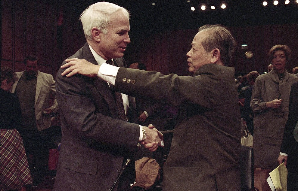 "FILE - In this Nov. 7, 1991, file photo, Sen. John McCain, R-Ariz., left, is hugged by former North Vietnam Col. Bui Tin on Capitol Hill in Washington after a hearing of the Senate Select Committee on POW and MIA affairs. Tin oversaw a military prison operation dubbed the ""Hanoi Hilton,"" where McCain was held prisoner during the Vietnam War. McCain, the war hero who became the GOP's standard-bearer in the 2008 election, died Saturday, Aug. 25, 2018. He was 81. (AP Photo/Dennis Cook, File)"