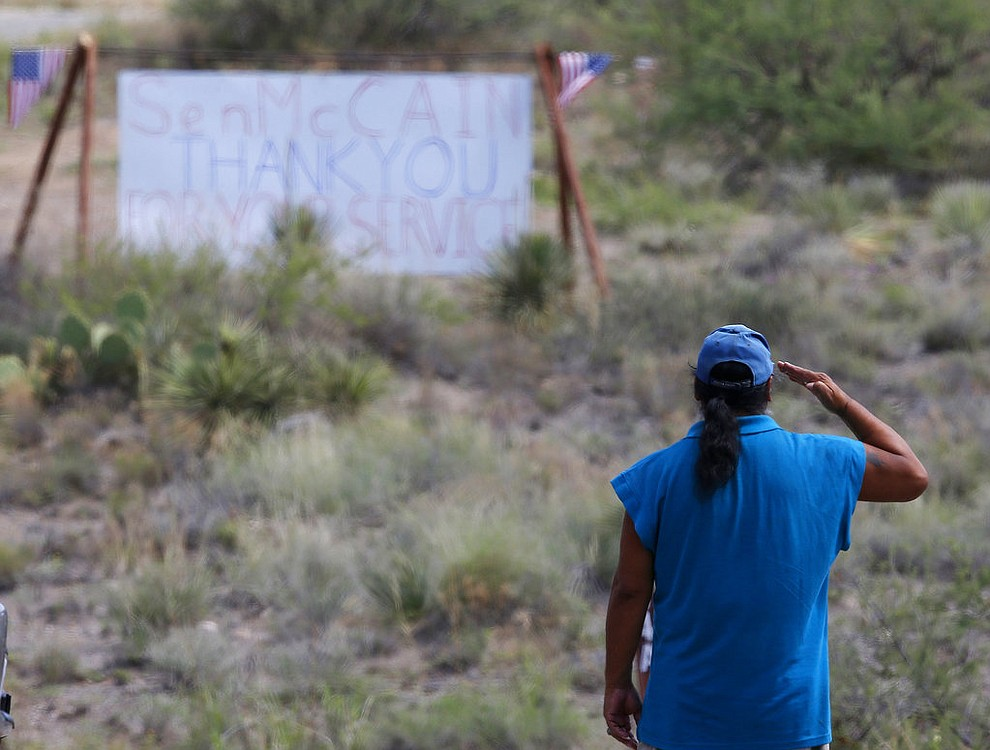 A military veteran pays his respects, as John McCain has discontinued medical treatment for an aggressive form of brain cancer, at the entrance to the McCain ranch complex in Cornville, Ariz., Saturday, Aug. 25, 2018. Arizona Sen. McCain, the war hero who became the GOP's standard-bearer in the 2008 election, has died. He was 81. His office says McCain died Saturday, Aug. 25, 2018. He had battled brain cancer. (AP Photo/Ross D. Franklin)