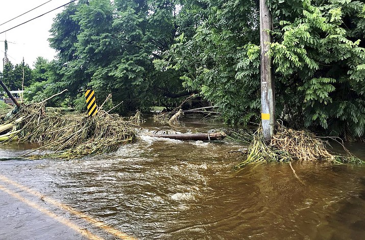 In this photo provided by Jessica Henricks, is flooding and damage from Hurricane Lane Friday, Aug. 24, 2018, near Hilo, Hawaii. Hurricane Lane barreled toward Hawaii on Friday, dumping torrential rains that inundated the Big Island's main city as people elsewhere stocked up on supplies and piled sandbags to shield oceanfront businesses against the increasingly violent surf. The city of Hilo, population 43,000, was flooded with waist-high water. (Jessica Henricks)