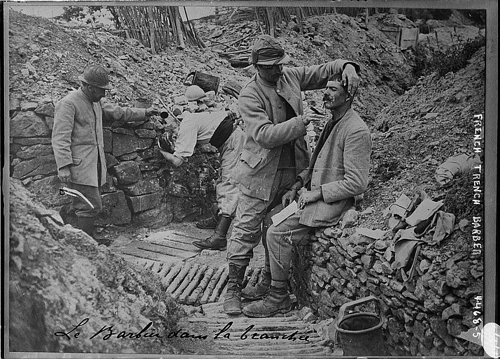 Hundreds of volunteers from 18 countries gathered in the northeastern French town of Verdun on Saturday to keep alive the memory of those who fought under appalling conditions in World War I. In the photo above a barber is shaving soldiers in a French trench. (Photo courtesy of Bain News Service [Public domain], via Wikimedia Commons)