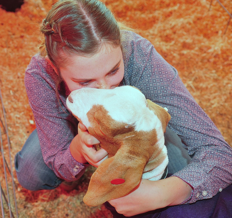 Chino Valley FFA's Arley Tucker gives her market goat a kiss at the 69th annual Yavapai County 4-H/FFA Expo Show and Auction Saturday, August 25, 2018 at the Prescott Rodeo Grounds. (Les Stukenberg/Courier)
