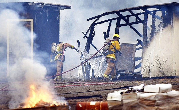 This Friday, Aug. 24, 2018 photo shows firefighters take care of damage at the Hawaiian Dredging base yard in Puamana, Hawaii. Several early morning fires, fed by winds from an approaching Hurricane Lane, destroyed several homes and buildings, including some at the construction company base yard. (Matthew Thayer/The Maui News via AP)