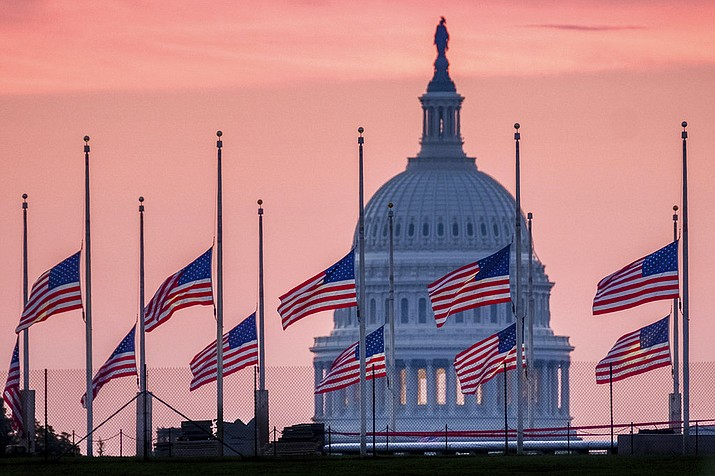 Flags flying a half-staff in honor of Sen. John McCain, R-Ariz., frame the U.S. Capital at daybreak in Washington, Sunday, Aug. 26, 2018. McCain, 81, died at his ranch in Arizona after a yearlong battle with brain cancer. (AP Photo/J. David Ake)