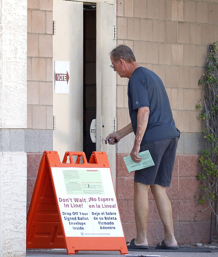 A man drops off his ballot at a polling station, Tuesday, Aug. 28, 2018, in Phoenix. Equipment issues and a shortage of workers should not delay release of results; however, those still in line may learn of who won before they cast their ballots. (Matt York/AP)